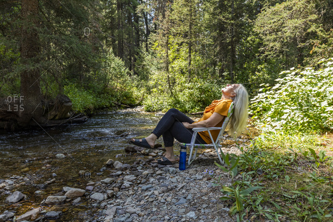 USA, Idaho, Sun Valley, Woman sitting on chair on riverbank in forest