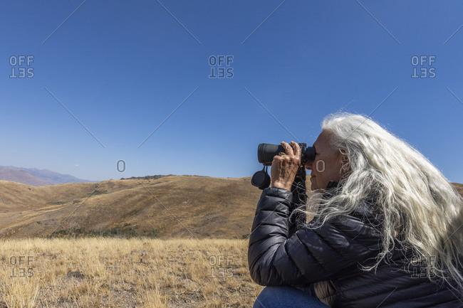 USA, Idaho, Bellevue, Woman looking through binoculars in desert