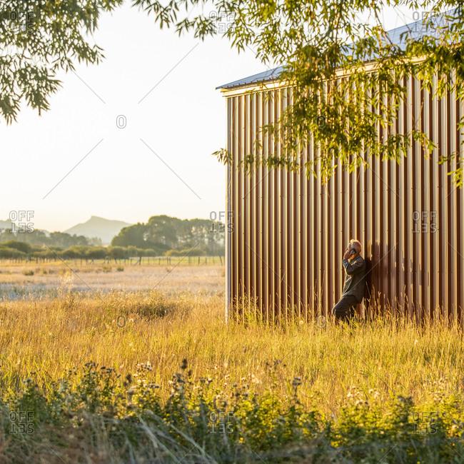 USA, Idaho, Bellevue, Farmer leaning against farm building and talking on phone