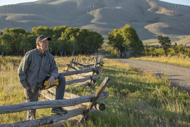 USA, Idaho, Bellevue, Farmer leaning against fence on field