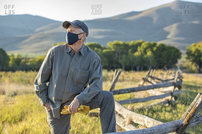 USA, Idaho, Bellevue, Farmer in face mask leaning against fence on field