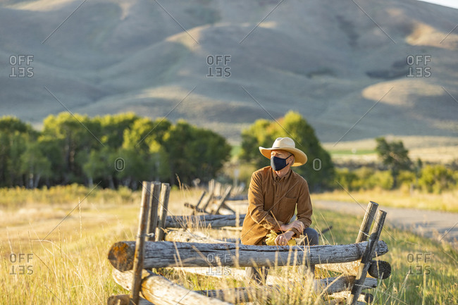 USA, Idaho, Bellevue, Rancher in face mask leaning against fence on field