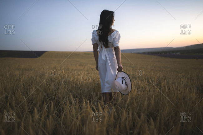 France, Young woman in white dress standing in cereal field