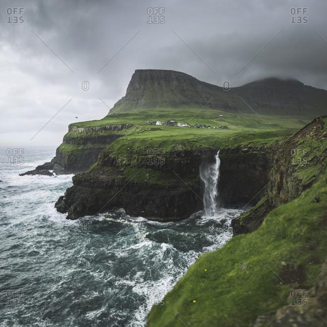 Denmark, Faroe Islands, Gasadalur village, Mulafossur Waterfall, Mulafossur Waterfall falling from cliff into ocean