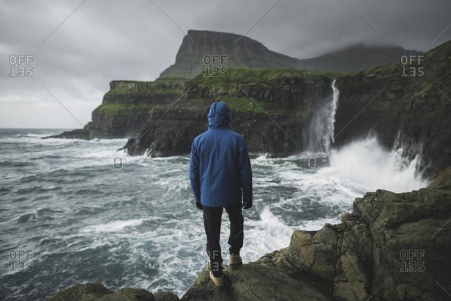 Denmark, Faroe Islands, Gasadalur village, Mulafossur Waterfall, Man standing on cliff and looking at Mulafossur Waterfall falling into ocean