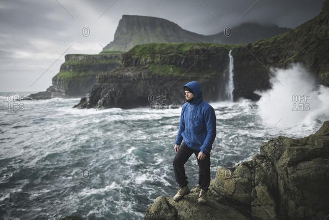 Denmark, Faroe Islands, Gasadalur village, Mulafossur Waterfall, Man standing on cliff with Mulafossur Waterfall in background