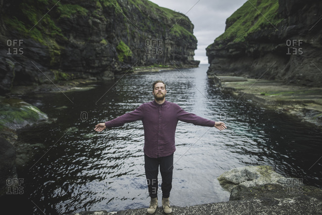 Denmark, Faroe Islands, Gjgv, Man standing inn gorge with outstretched arms