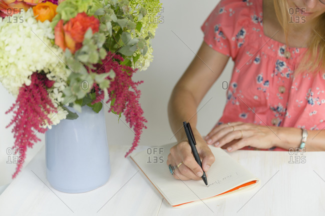 Woman writing in note pad