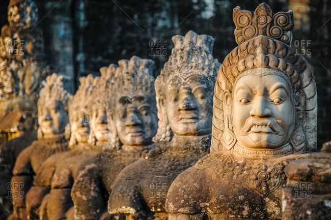Ancient carved faces on south gate of Angkor Thom. Bad gods in hindu epic tale of a tug of war between good vs evil in the story the churning of the sea of milk.