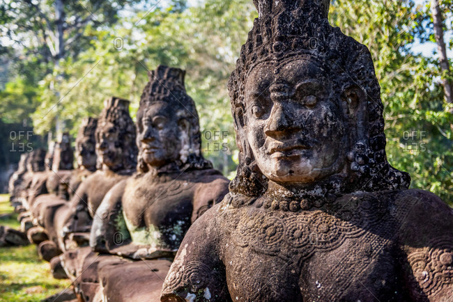 Angkor Archaeological Park, Siem Reap, Cambodia. Bad gods line the bridge leading to north gate of Angkor Thom a tug of war between good vs evil in the story the churning of the sea of milk.