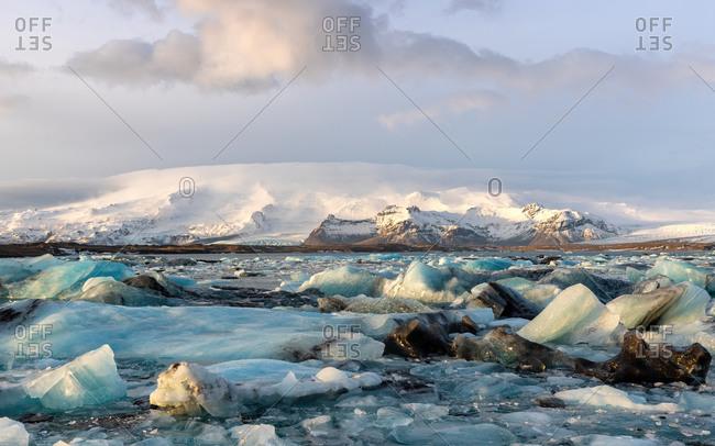 Icebergs in the Jokulsarlon glacial lagoon, bordering Vatnajokull National Park in southeastern Iceland, part Vatnajokull Glacier with surrounding snow-covered mountain.
