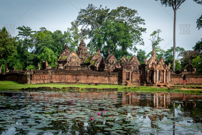 Angkor archaeological Park, Siem Reap, Cambodia. Tourist takes photograph of east entrance to Banteay Srey temple with lous flowers in moat as foreground.