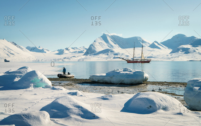 A sailing expedition boat and zodiac stop at Gjerstenodden. As seen on a glacier hike during an Arctic Spring cruise through North Spitsbergen, Svalbard.
