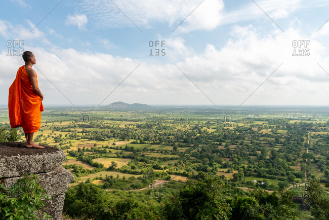 16 December 2013: Monk stands on Phnom Chisor, over looking Cambodian countryside in direction of main entrance. Samraong District, Cambodia.