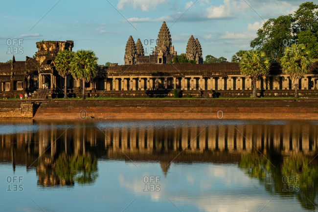 Angkor Archaeological Park, Siem Reap, Cambodia. Main entrance of Angkor Wat against cloudy blue sky in late afternoon light from west side.
