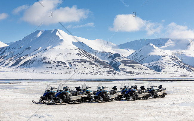 Snowmobiles on the ice at the edge of the fjord, Longyearbyen, Svalbard. Pristine snow covered mountains can be seen in the background.