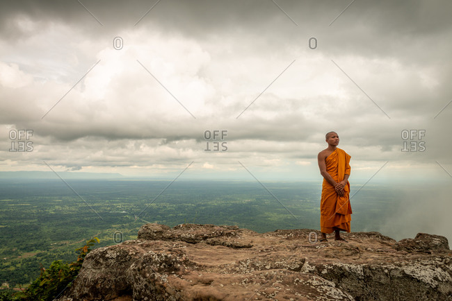 PREAH VIHEAR, CAMBODIA - 12 August 2013: Novice Monk stands on plateau's edge at  Preah Vihear temple over looking plains of Cambodia.