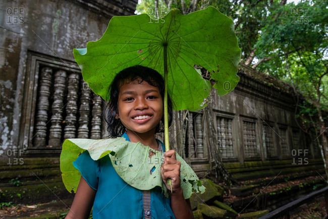SIEM REAP, CAMBODIA - 16 June 2014: Beng Mealea, Angkorian Temple, Siem Reap province.: Local girl uses lilly pond leave as umbrella.