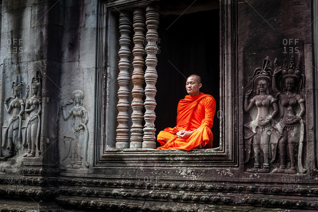 SIEM REAP, CAMBODIA - 07 July 2012: Monk meditating in window of court yard in Angkor Wat surrounded by apsara dancer figures.
