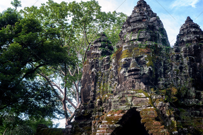 Angkor Archaeological Park, Siem Reap, Cambodia. Close up of Buddha's face on north gate of Angkor Thom surrounded by trees.