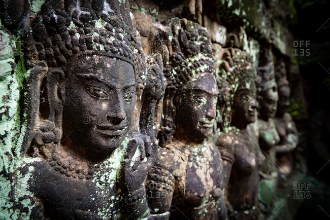 Angkor Archaeological Park, Siem Reap, Cambodia. Buddha's face seen through jungle trees on north gate of Angkor Thom.