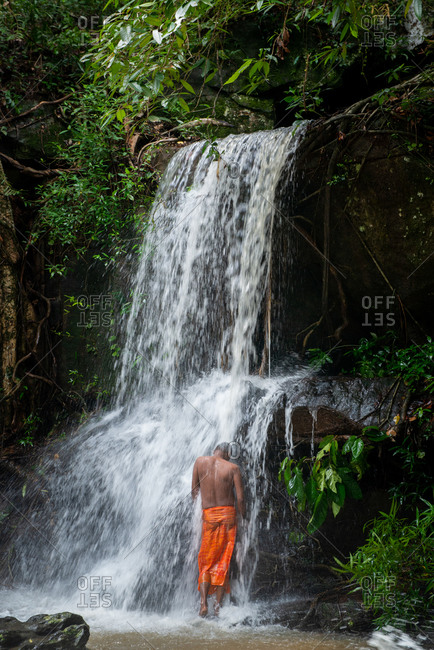 SIEM REAP, CAMBODIA - 27 September 2013: Man cleansing in waterfall at Kbal Spean. Angkorian site, Siem Reap province