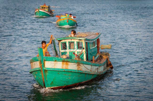KAMPOT PROVINCE, CAMBODIA - 07 February 2012: Fishing boats leave on evening tidal waters for a full nights fishing.