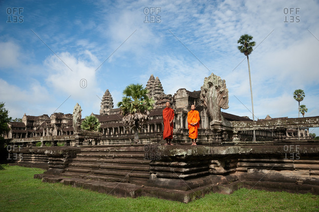 SIEM REAP, CAMBODIA - 07 July 2012: Monks on steps of north east entrance to Angkor Wat in morning sun light.