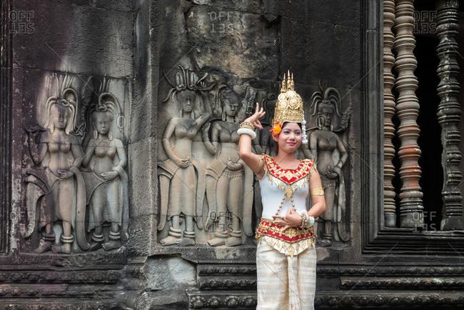 ANGKOR WAT, CAMBODIA - 16 November 2013: Modern Apsara dancer posing in front of ancient Apsara carvings.