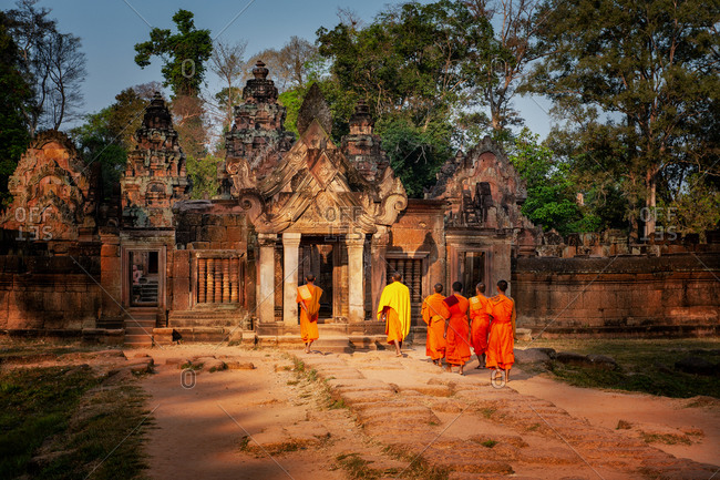 Angkor archaeological Park, Siem Reap, Cambodia. Monks enter Basnteay Srey temple in early morning light.