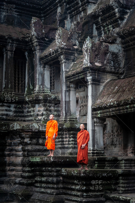 SIEM REAP, CAMBODIA - 07 July 2012: Monks stand in lower court yard of cruciform galleries in Angkor Wat