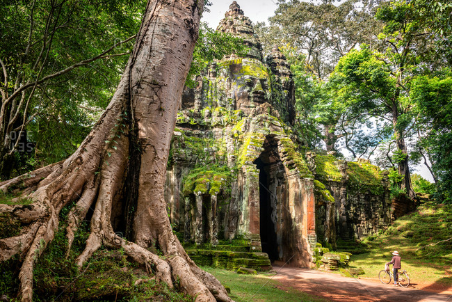 Angkor Archaeological Park, Siem Reap, Cambodia. Local rides bicycle through north gate of Angkor Thom.