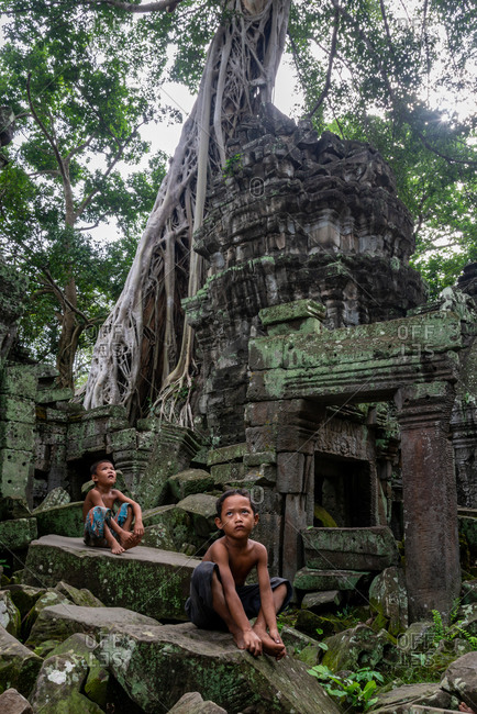 TA PROHM, ANGKORIAN TEMPLE, SIEM REAP, CAMBODIA - 29 June 2014: Local kids hang out in temple grounds.