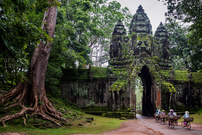 Angkor Archaeological Park, Siem Reap, Cambodia. Locals cycle home through north gate of Angkor Thom.