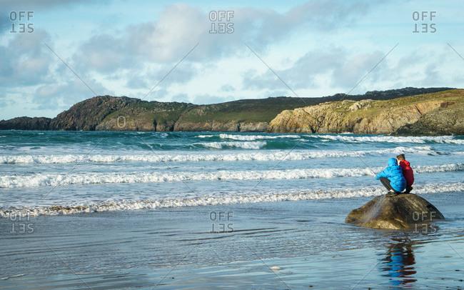 Boys look out at the ocean, Pembrokeshire Coastal Path, near St David's, Pembrokeshire, Wales, UK.