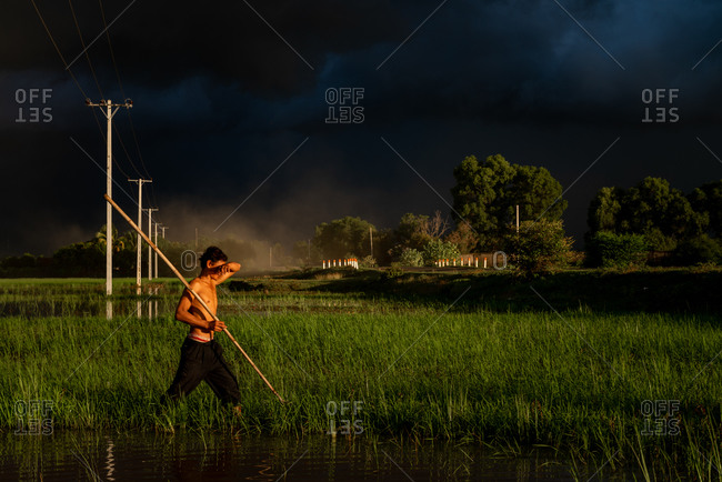 KOMPONG THOM, CAMBODIA - 2013 June 27: A farmer makes his way home as a monsoon storm is brewing.