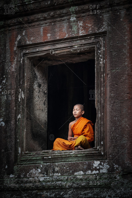 SIEM REAP, CAMBODIA - 21 January 2014: Monk meditates in window at north gate of Angkor Wat.