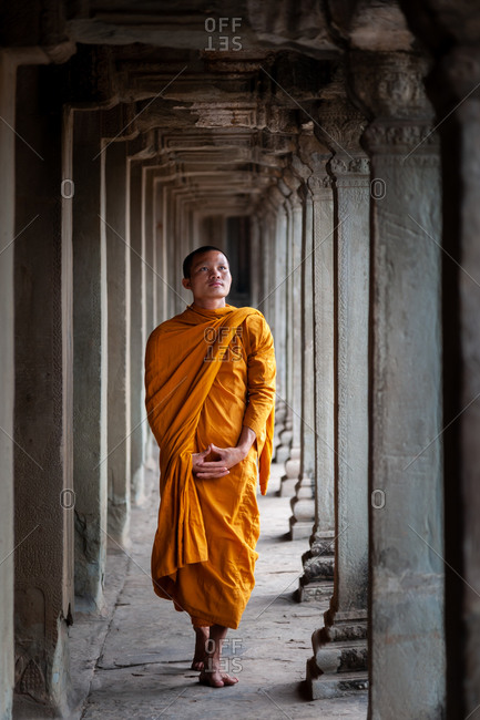 SIEM REAP, CAMBODIA - 10 March 2012: Monk walks in east wing of north gallery in Angkor Wat