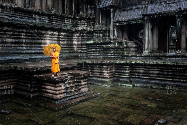 SIEM REAP, CAMBODIA - 28 September 2013: Monk braves rain in  Angkor Wat  open court yard.