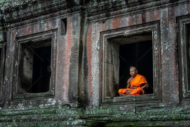 SIEM REAP, CAMBODIA - 06 August 2013: Monk mediates in window of north gate in Angkor Wat