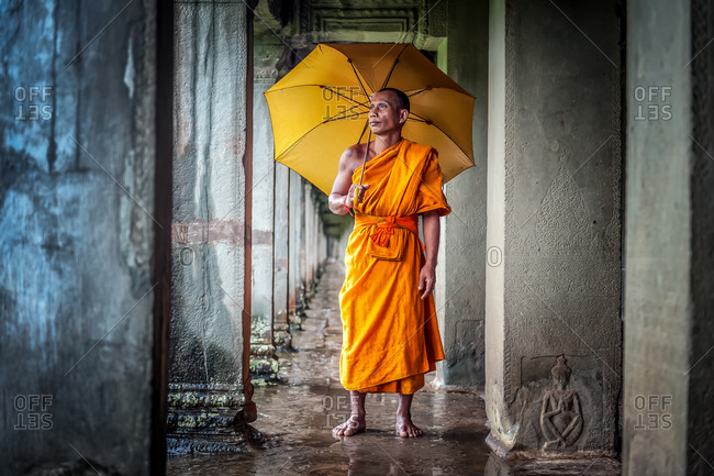 SIEM REAP, CAMBODIA - 28 September 2013: Monk shelters from rain in  Angkor Wat gallery.