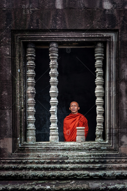 SIEM REAP, CAMBODIA - 07 July 2012: Monk stands in window of court yard  in Angkor Wat