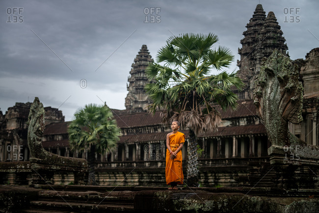 SIEM REAP, CAMBODIA - 22 June 2013: Monk standing north west entrance to Angkor Wat.