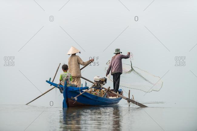 KAMPOT PROVINCE, CAMBODIA - 08 January 2014:  Family fish from small boat with net.