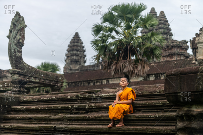 SIEM REAP, CAMBODIA - 22 June 2013: Monk sitting north west entrance to Angkor Wat.