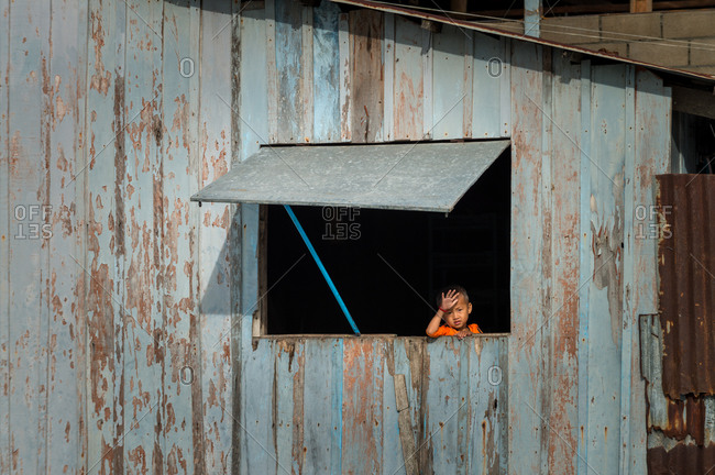 KAMPOT PROVINCE, CAMBODIA - 18 December 2013: Small boy waves from his window.