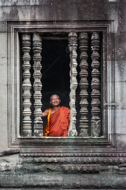SIEM REAP, CAMBODIA - 14 SEPTEMBER 2010:  Monk smiling in Angkor Wat window.