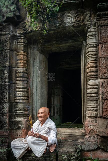 PREAH KHAN, ANGKOR PARK, CAMBODIA - 17 November 2013: Nun praying in doorway