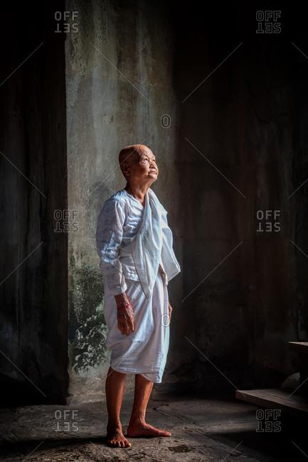 SIEM REAP, CAMBODIA - 15 September 2012: Nun in door way light of Angkor Wat