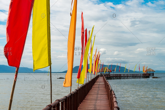 Kampot province, Cambodia. Long pier with decorative flags snake out to sea.
